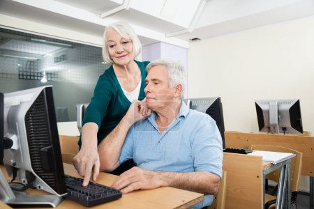 Woman Helping Male Classmate In Computer Lab
