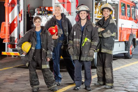 Portrait Of Confident Firefighters Standing Against Truck