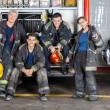 Full length portrait of confident firefighters by ...