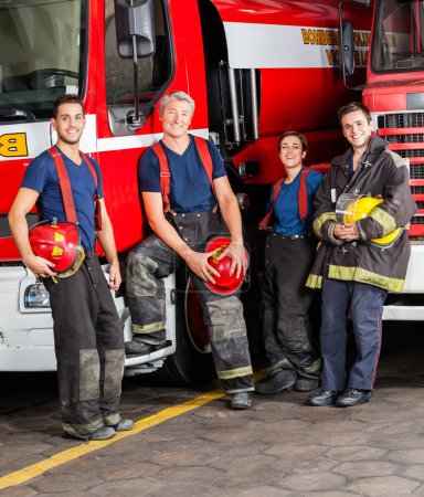 Portrait Of Smiling Firefighters Leaning On Trucks