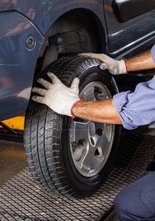 Photo pour Image recadrée du mécanicien masculin ajustant le pneu de voiture au garage - image libre de droit