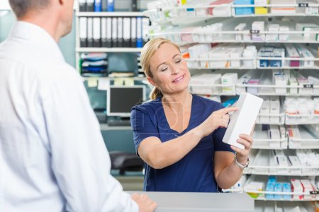 Photo for Smiling female pharmacist showing details of product to customer in pharmacy - Royalty Free Image
