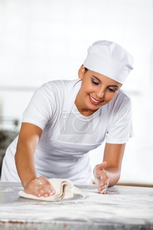 Female Baker Cleaning Table In Bakery