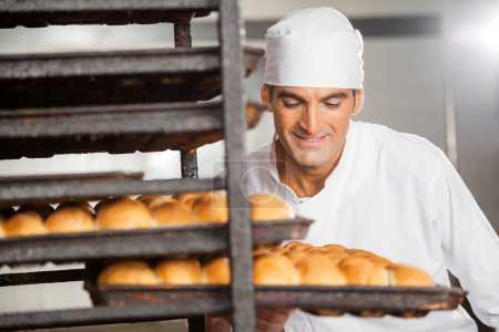 Photo for Smiling male baker removing baking tray from rack in bakery - Royalty Free Image