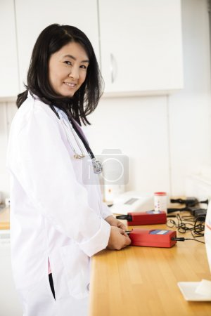 Photo pour Portrait de confiance femme médecin examinant l'échantillon de sang dans la machine à la clinique - image libre de droit