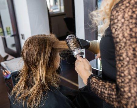 Photo pour Image recadrée de coiffeur coiffant les cheveux des clients avec sèche-cheveux et brosse dans le salon - image libre de droit