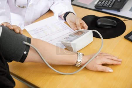 Photo for Cropped image of female doctor examining patients blood pressure in clinic - Royalty Free Image