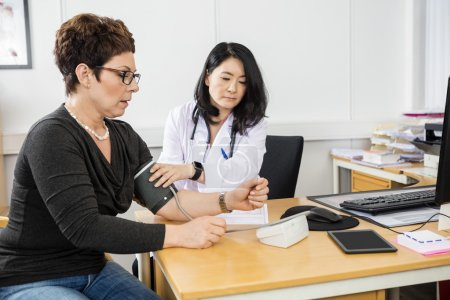 Doctor Examining Female Patients Blood Pressure