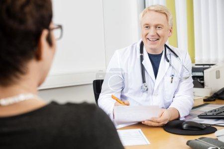 Photo pour Heureux docteur mature regardant patiente au comptoir en clinique - image libre de droit