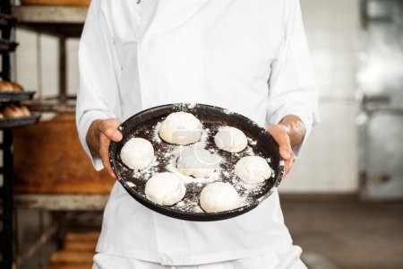 Photo for Midsection of male baker showing dough balls in tray at bakery - Royalty Free Image