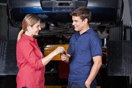 Happy Customer Giving Car Key To Mechanic