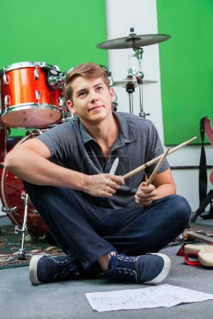 Thoughtful Professional Holding Drumsticks While Sitting On Floo