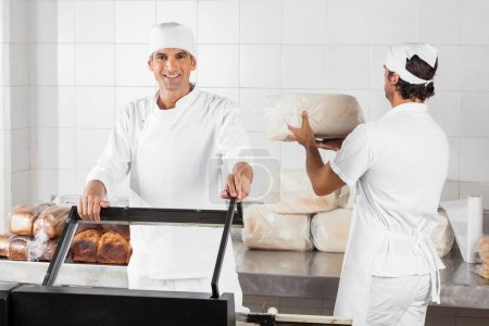 Photo for Portrait of confident male baker using vacuum seal machine while coworker working in bakery - Royalty Free Image