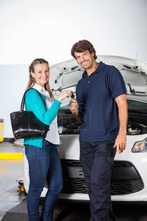 Happy Customer Giving Car Keys To Technician