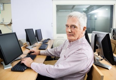 Portrait Of Confident Senior Student Sitting At Desk In Classroo