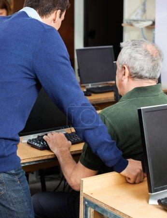 Teacher Assisting Senior Man At Computer Desk