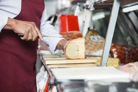 Salesman Slicing Cheese In Shop