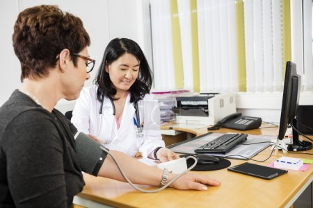 Physician Looking At Patient While Examining Her Blood Pressure