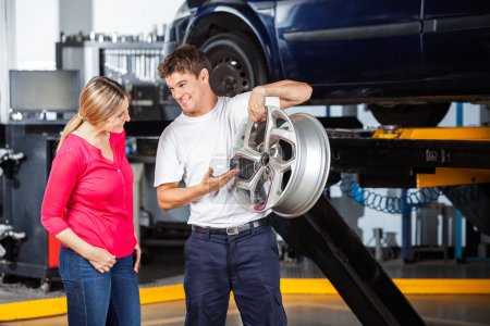 Mechanic Explaining Hubcap To Customer