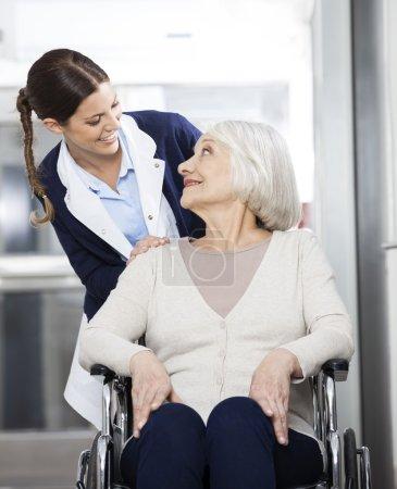 Photo pour Joyeuse physiothérapeute regardant une patiente âgée assise en fauteuil roulant dans un centre de réadaptation - image libre de droit