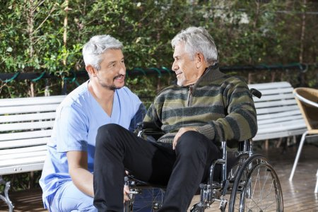 Photo for Mature male physiotherapist looking at disabled senior man in wheelchair at rehab center lawn - Royalty Free Image