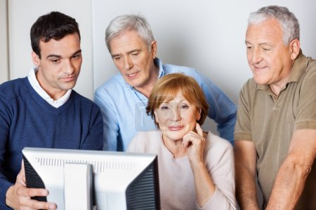 Photo pour Tuteur masculin aidant les personnes âgées à utiliser l'ordinateur en classe - image libre de droit