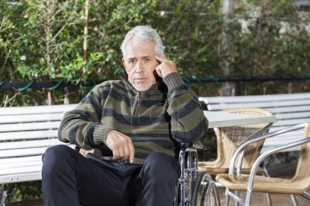 Pensive Senior Male Patient Sitting In Wheelchair At Lawn