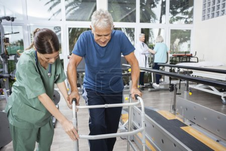 Nurse Assisting Senior Man To Walk Using Walker
