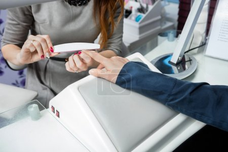 Midsection Of Beautician Filing Clients Nail