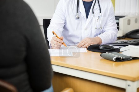 Midsection Of Doctor Writing Prescription For Patient At Desk