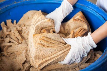 Bakers Hands Discarding Bread Waste In Garbage Bin