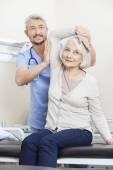 "Постер, картина, фотообои ""Физиотерапевт, помогая старшим пациента с руку упражнения"""