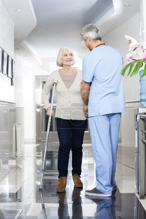 Physiotherapist Helping Senior Patient With Crutches