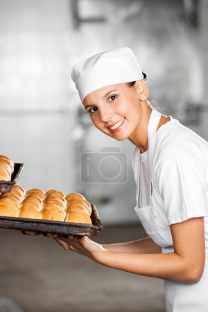 Photo for Side view of happy female baker with fresh breads in baking tray at bakery - Royalty Free Image