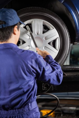Photo for Rear view of male technician filling air into car tire at garage - Royalty Free Image