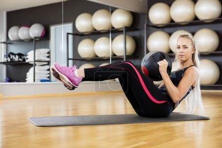 Portrait Of Woman Exercising With Medicine Ball In Gym