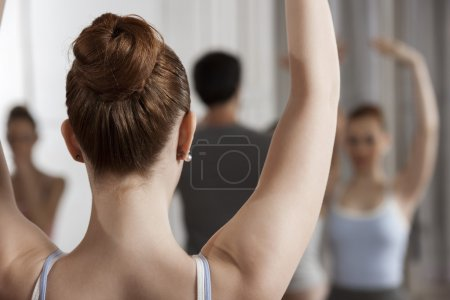 Ballet Dancer Raising Arms In Dance Studio