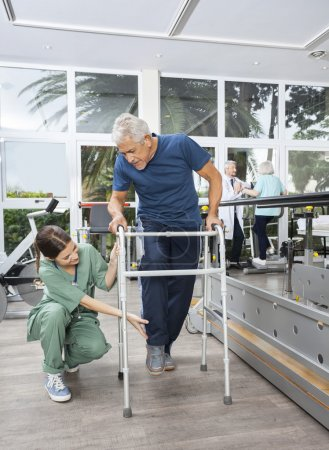 Female Nurse Helping Senior Patient With Walker In Fitness Studi