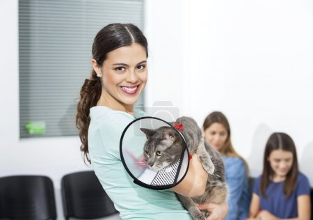 Woman Holding Cat With Cone