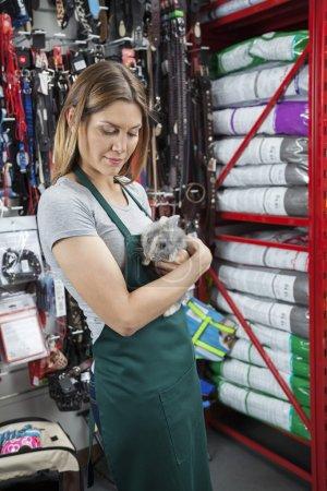 Saleswoman Holding Rabbit At Pet Store