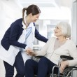 Friendly physiotherapist consoling senior woman si...