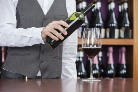 Bartender Pouring Red Wine In Glass At Counter