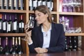 Zákazník vonící červené víno na čítač v seznamu vybrat vinařství