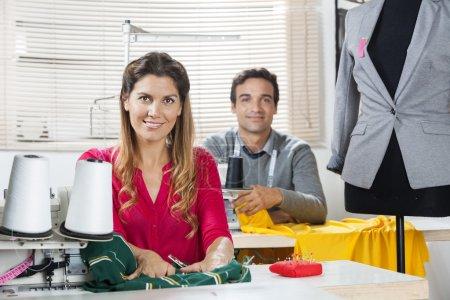 Photo pour Portrait de confiant mâle et femelle tailleurs séance à établis dans l'usine de couture - image libre de droit
