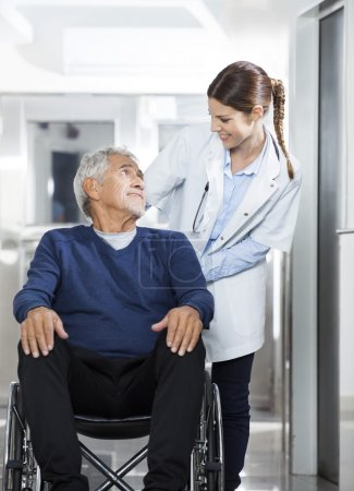 Photo for Smiling female doctor looking at senior patient on wheelchair at rehab center - Royalty Free Image