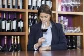 Zákazník vonící červené víno u pultu v obchodě