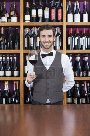 Bartender Holding Red Wine Glass At Counter