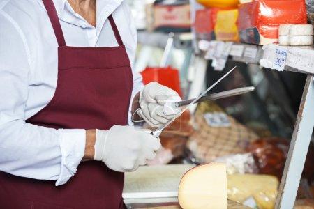 Senior Man Sharpening Knives In Cheese Shop