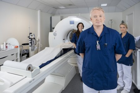 Confident Male Doctor With Colleagues Standing By MRI Machine