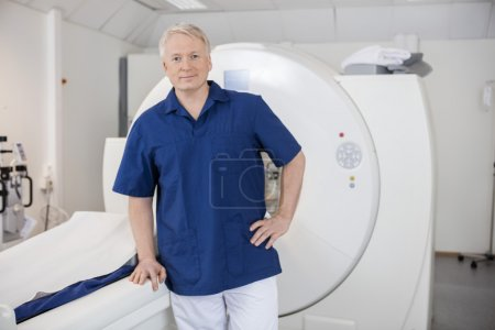 Male Confident Radiologist Leaning On MRI Machine